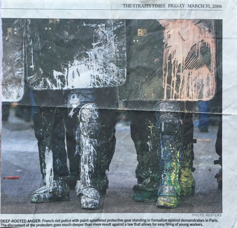 9d. The Straits Times. Friday March 31  2006. @Reuters. Deep-rooted anger. French riot police with paint-splattered protective gear standing in formation against demonstrators in Paris. 4959_1024